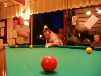 Man about to hit the ball playing Pool