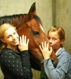 Two young ladies, one kissing a horse
