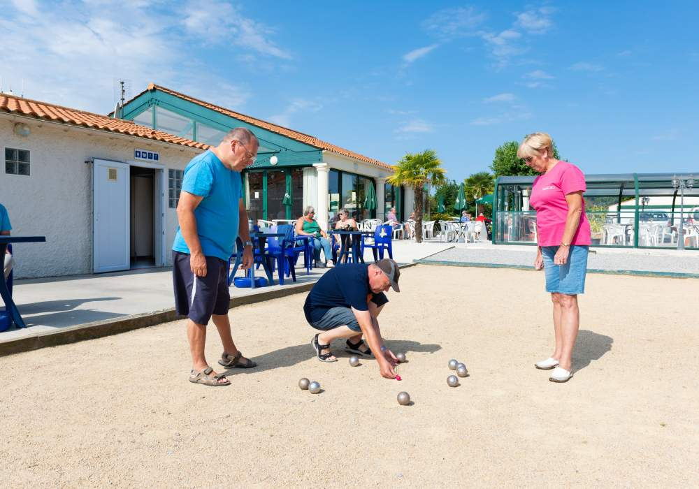 Man leaning down, pointing at Bocce Ball